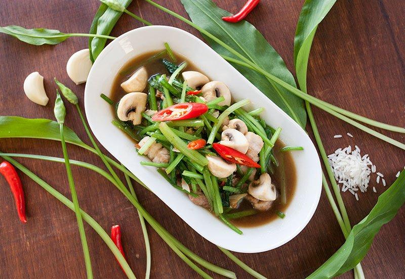 A plate of Pad Tom Gratiem (wild garlic stir fry) from our Thai cafe menu