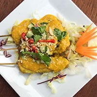 A plate of chicken satay with satay sauce from Khao Soi Thai Cafe starter menu