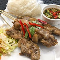 Skewers of Moo Ping, marinated pork strips, grilled and served with a dip